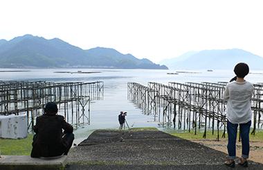 右から写真家笹岡啓子、映像収録する佐藤英和、左端に、ただ茫然とヒビを仕掛けた遠浅のイソを眺める豊島重之。