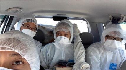 帰還困難区域に向かう車内のGGM:防護服の4人  photo by 山川冬樹
